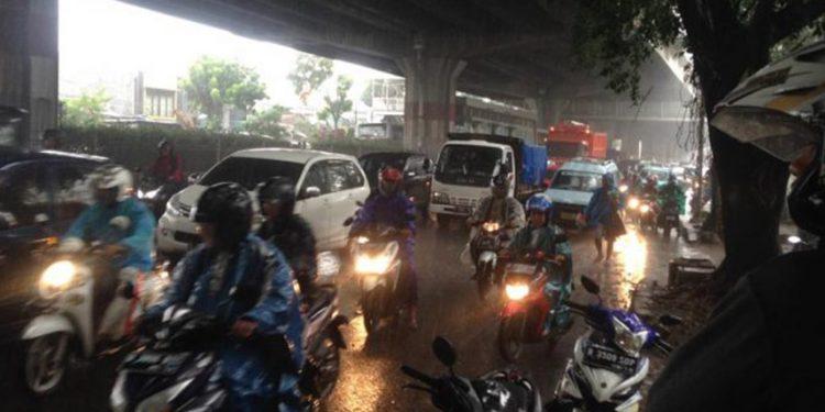 pengendara motor saat musim hujan dan angin kencang